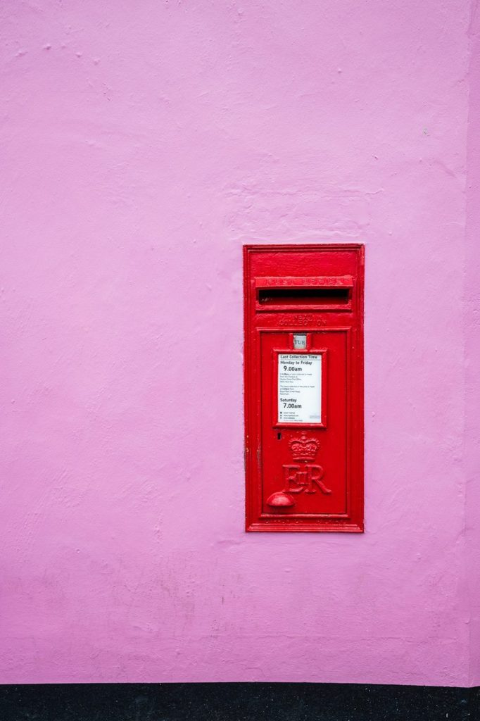 Postbox in lilac wall