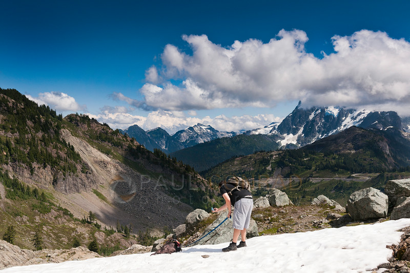 © Paul Conrad/Pablo Conrad Photography - Taking a break in Herman's Saddle, Zach takes photos of Domino as he lays in a snowfield. The peaks of Mt. Shuksan are shrouded by clouds. You can also see the road to Artist's Point on the left. You can see Mt. Sefrit and Nooksack Ridge in the background.
