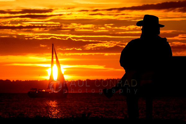 © Paul Conrad/Pablo Conrad Photography - A man watches a sailboat traverse the setting Sun while ejoying a front row seat of a gorgeous sunset at Boulevard Park in Bellingham, Wash., on Sunday Aug. 25, 2013.