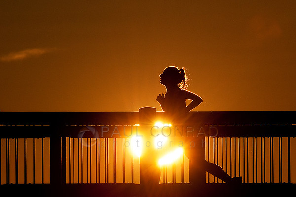 A runner jogs along the Boardwalk at Boulevard Park in Bellingham, Wash., during a blazing Sunset on Sunday evening April 14, 2013. (© Paul Conrad/ Paul Conrad Photography) bellingham photographer, bellingham wedding photographer