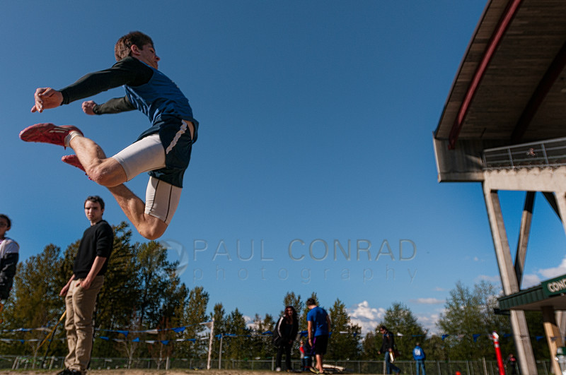© Paul Conrad/ Pablo Conrad Photography - Sedro-Woolley's Mason Elms flys over the landing pit of the long jump during finals at the NWC track & field meet at Civic Field and Stadium in Bellingham, WA. Elms won 4th place with a distance of 20 feet, 3 inches.