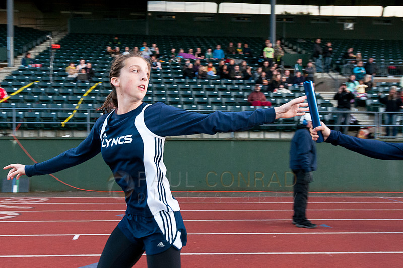 © Paul Conrad/ Pablo Conrad Photography - Lynden Christian's Brianna Bruneau gets the baton from Emily Sytsma during the final lap of the Girl's 4x400 realy at the NWC track & field meet at Civic Field and Stadium in Bellingham, Wash. The Lynden Christian team of four won First Place with a time of 4 min and 7.29 secs.
