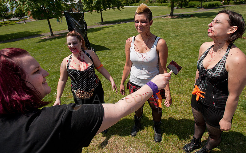© Paul Conrad/The Bellingham Herald - Make-up artists Stephanie Matteson, lfet, with Scary Larry Productions spatters blood onto Jackie Kersten, Jaime Inslee, and Monica Lawson during the fifth annual Zombies vs. Survivors game at Maritime Heritage Park in Bellingham, Wash., on Saturday afternoon May 31, 2014.