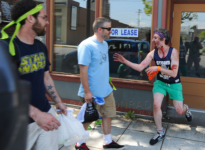 © Paul Conrad/The Bellingham Herald - Brain Drain team member Brendan Lavotz, right, of Bellingham jumps out of his hiding spot and attacks survivors during Zombies vs. Survivors in downtown Bellingham on Saturday  May 31, 2014, in Bellingham, Wash.
