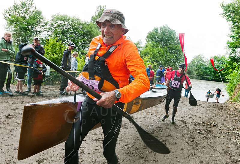 © Paul Conrad/The Bellingham Herald - Nick Bauer, left, and Jim Bauer carry their canoe out of the Nooksack River to begin the cross country 3biking leg of the 2014 Ski to Sea Race on Sunday, May 25, 2014 in Ferndale, Wash.