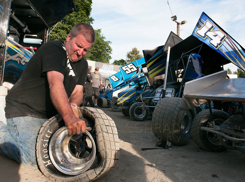 Kurt Erickson of Port Orchard, Wash., struggles to change a tire during the 2014 Clay Cup Nationals at Deming Speedway in Everson, Wash., on Thursday evening July 17 , 2014. The Clay Cup Nationals mini sprint  races continue through Saturday July 19th.