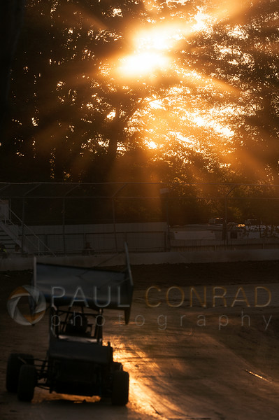 The Sun filters through trees while a racer rounds the course during the 2014 Clay Cup Nationals at Deming Speedway in Everson, Wash.,  on Thursday evening July 17 , 2014. The Clay Cup Nationals mini sprint  races continue through Saturday July 19th.