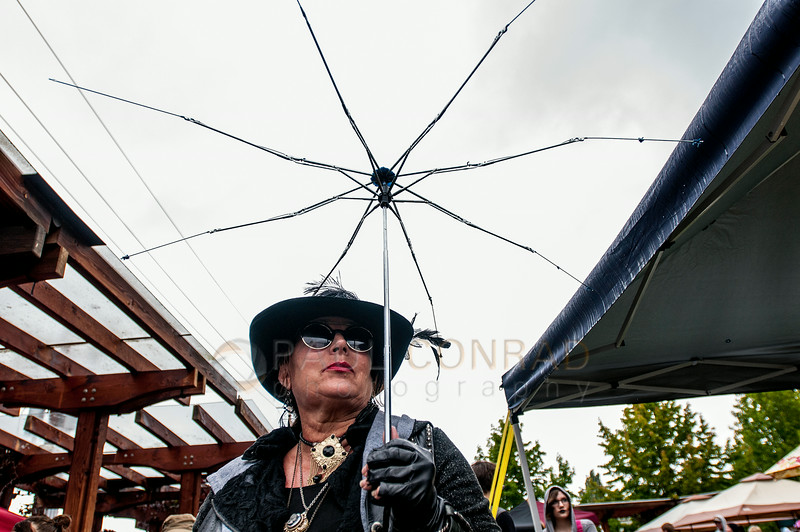 © Paul Conrad/The Bellingham Herald - Valerie Snelling of Bellingham takes in the surroundings during the Fairhaven Steampunk Festival at Fairhaven Village Green in Fairhaven, Wash., on Saturday afternoon July 19, 2014. Snelling says this was her first time dressing in Steampunk fashion and began working on her costume at midnight. Hundreds enjoyed the sights of individuals dressed in Steampunk Victorian costumes, live entertainment, food and vendors .