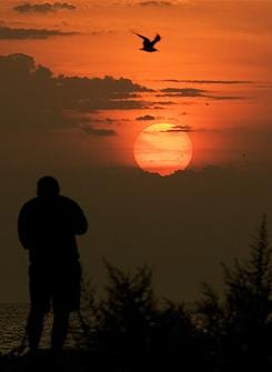 Randal Ruvalcaba of Brookfield, Wis., takes pictures of the sun rising over Lake Michigan Aug. 28, 2007 in Milwaukee. Ruvalcaba was out early to take pictures of the lunar eclipse.