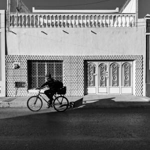 Man on a bicycle Walking in Merida MX by Birgit Pauli-Haack