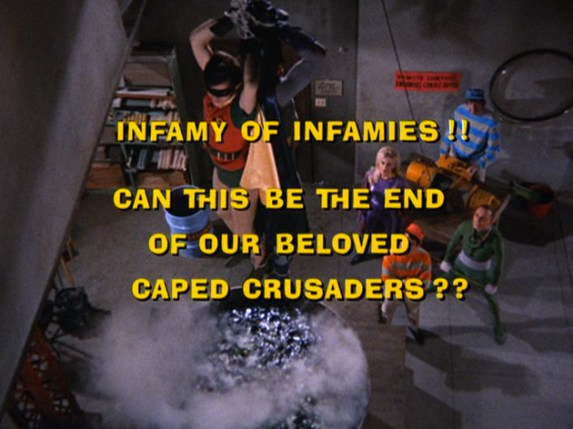 """A screenshot of the Batman TV series. In the background, the Riddler dangles Batman (Adam West) and Robin (Burt Ward) over a bubbling and steaming vat. In the foreground, yellow text asks: """"Infamy of Infamies!! Can this be the end of our beloved caped crusaders??"""""""