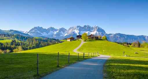 Idyllic alpine scenery, farmhouse in front of snowy mountains, Kitzbühel, Tyrol, Austria