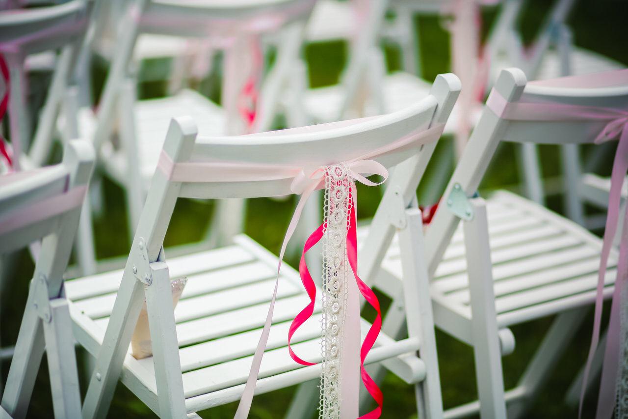 Liebevoll dekorierte Stühle bei einer Trauung im Freien. Foto: Goodvit