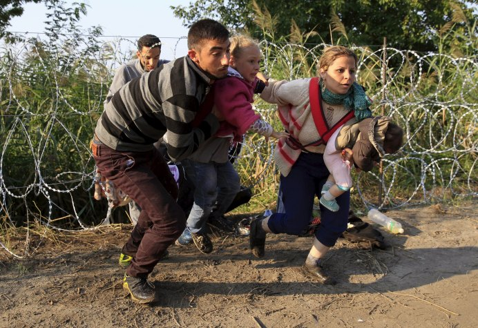Syrian migrants run after crossing under a fence as they enter Hungary, at the border with Serbia, near Roszke