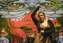 Tana Monti cantante de Victorina Sanada con una mano hacia arriba.