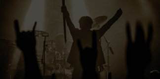 cantante de armored dawn, banda brasileña, sosteniendo una espada hacia abajo durante un concierto en vivo. a contraluz, se observan las manos del público haciendo la seña de cuernos.