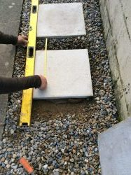 Once the stepping stone is laid in on the cement mixture check your measurements you saved earlier. Measure the distance between the slabs and gently move the slab into place
