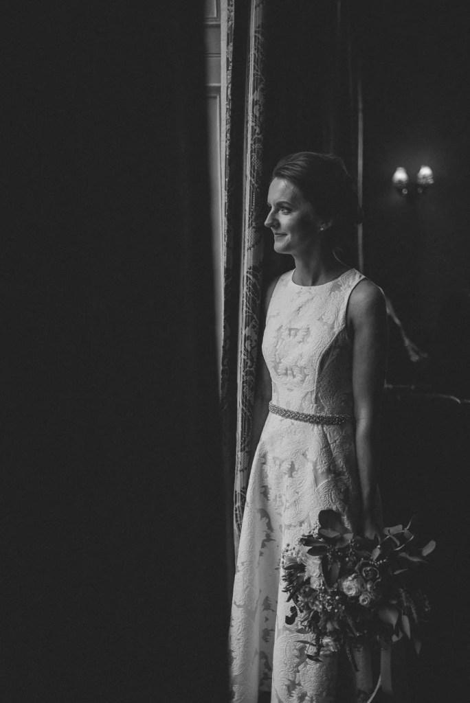 bride look at the window in Belleek Castle wedding venue