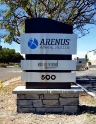 Arenus monument sign curved dimensional brushed aluminum panels on a faux stone base