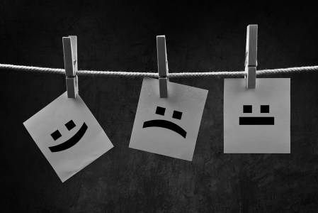 Emoticons printed on note paper attched to rope with clothes pins - happy, sad and neutral.