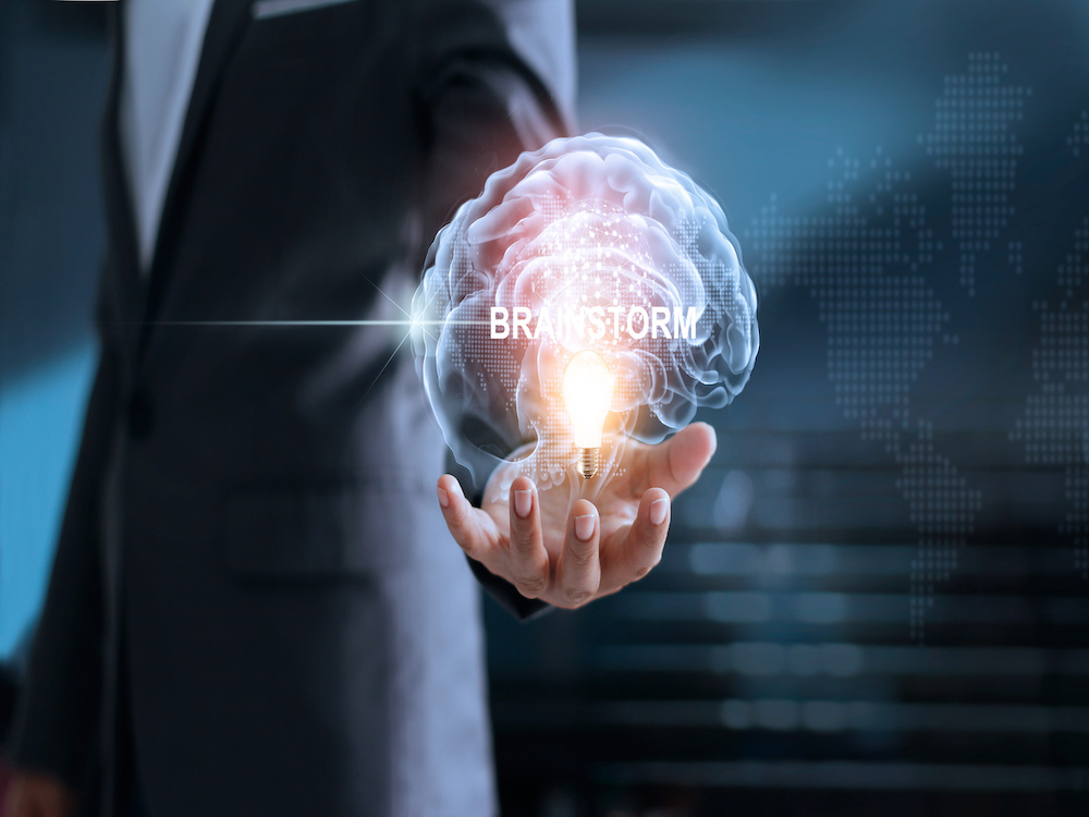 Businessman holding brain and light bulb with global networkIng connection, brainstorm and business concept