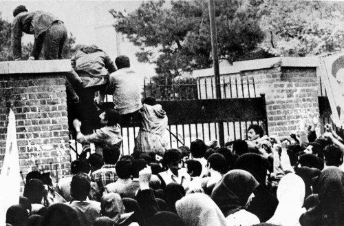 Iranian students climb over the wall of the U.S. embassy in Tehran during the Iranian Revolution, Nov. 4, 1979. The students went on to seize the embassy staff, and hold 52 of them hostage for 444 days. Photo by AFP/Getty Images