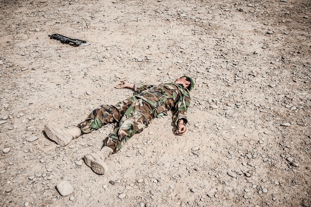 An Afghan soldier plays dead during a training exercise at Camp Hero in Kandahar. Despite its members getting paid three times the national average, the Afghan military has a high attrition rate due to desertion and combat deaths. Photo by Ben Brody/The GroundTruth Project