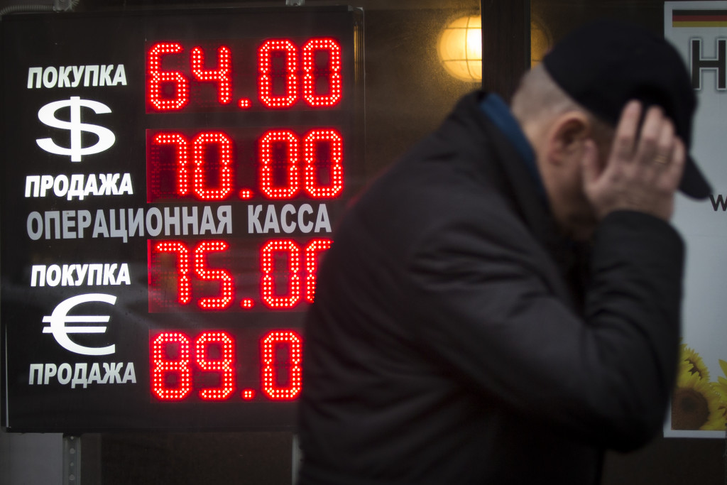 FILE - In this Tuesday, Dec. 16, 2014 file photo, a man walks by a sign advertising currencies of an exchange office in Moscow, Russia. Russia has been badly affected by the slide in oil prices in 2014 - the ruble has plunged despite big increases in interest rates as much of Russia's economy is based on energy. Sanctions on the country for its alleged involvement in the crisis in Ukraine haven't helped the economy either, which appears headed for recession. (AP Photo/Alexander Zemlianichenko, File )
