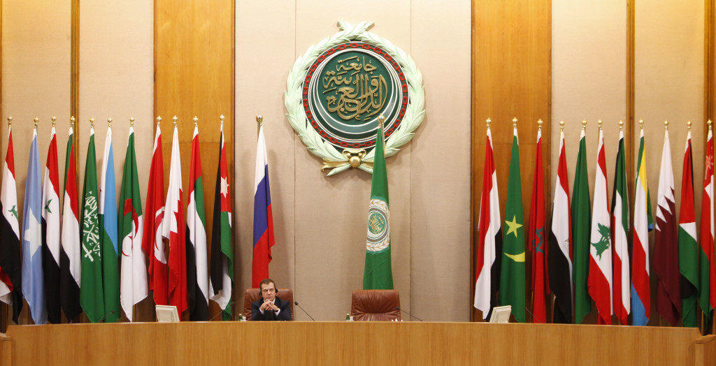 Backdropped with Arab countries flags and the logo of the Arab League, Russian President Dmitry Medvedev attends a meeting with Arab League representatives, unseen before delivers a speech, during a visit to Arab League headquarters in Cairo, Egypt, Tuesday, June 23, 2009. Medvedev, on a visit to Egypt, said Tuesday he sees some progress towards resolving the Israel-Palestinian dispute and is continuing to push for an international conference on the issue in Moscow. (AP Photo/Nasser Nasser)