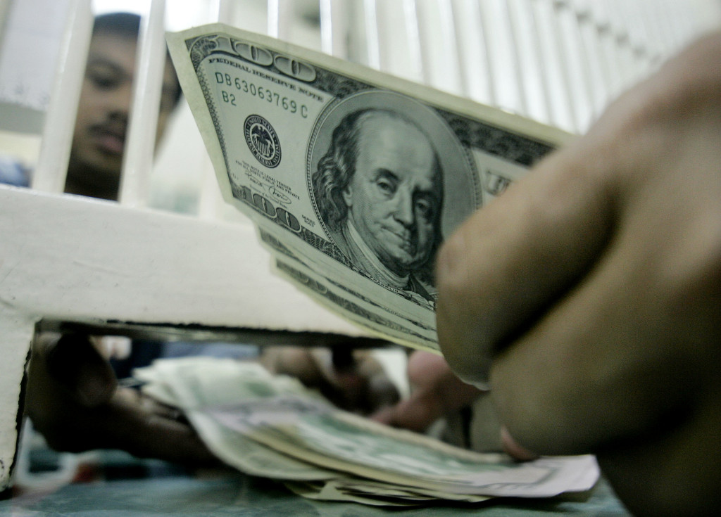 A man changes US dollars at a money changer in Manila on Tuesday July 5, 2005. The peso fell to a new six-month closing low against the U.S. dollar. The dollar finished at 56.245 pesos on the Philippine Dealing System, up from 56.090 Monday and the highest close since 56.255 on Jan. 6. The record low of 56.450 came in March 2004, during political uncertainty ahead of the presidential election.