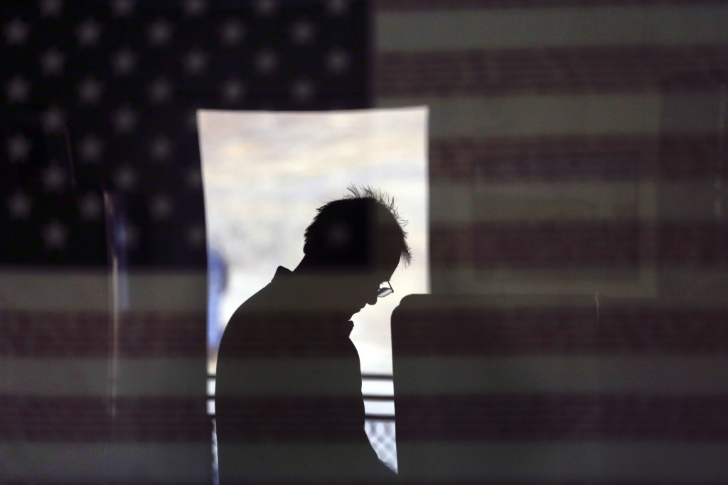 Hal Pigg is reflected in an image of a flag, as he casts his vote on Election Day, Tuesday, Nov. 6, 2012, in Jamul, Calif.  (AP Photo/Gregory Bull)