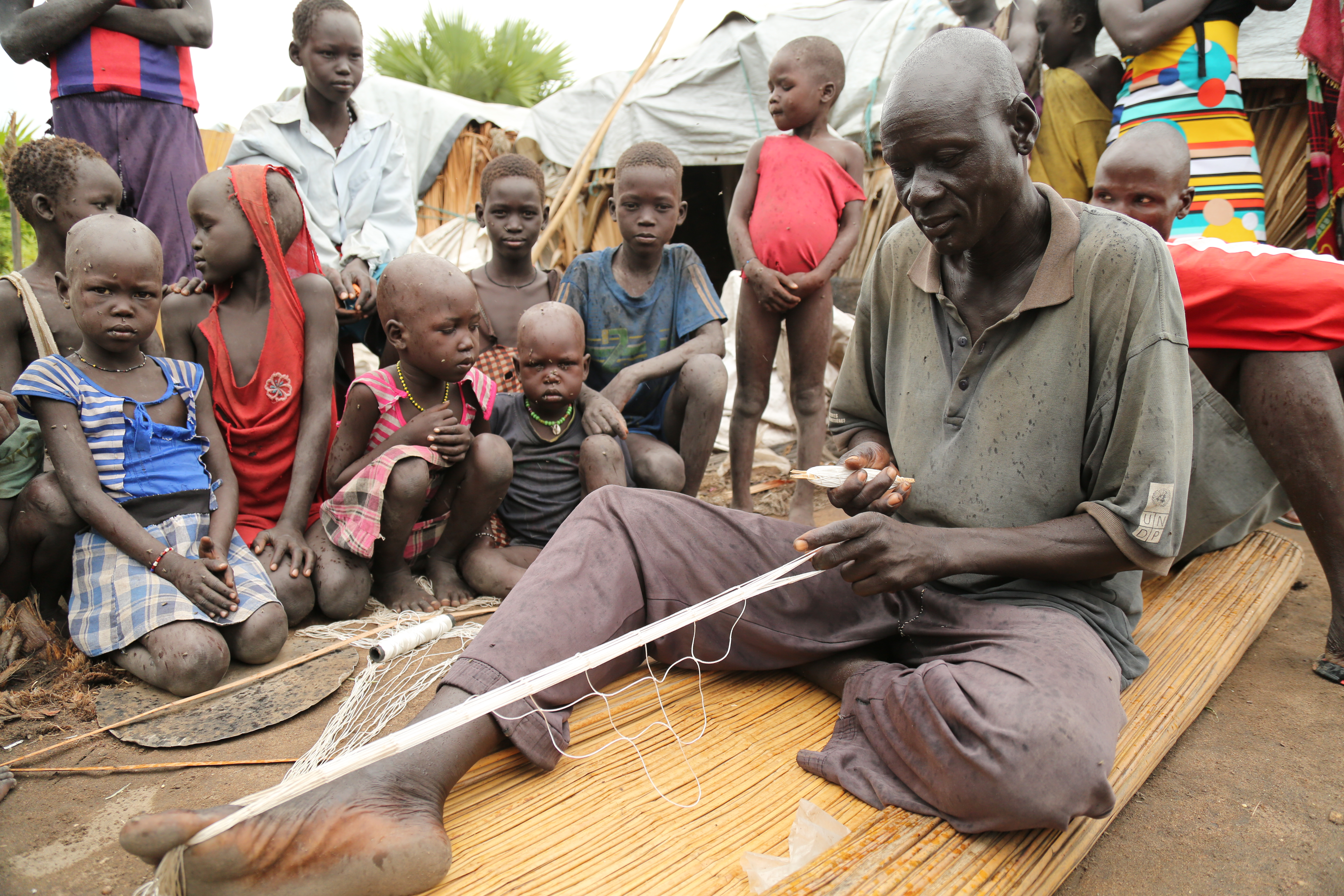 Peter Luak weaves a fishing net to help feed his family. (Photo: Marcelle Hopkins)