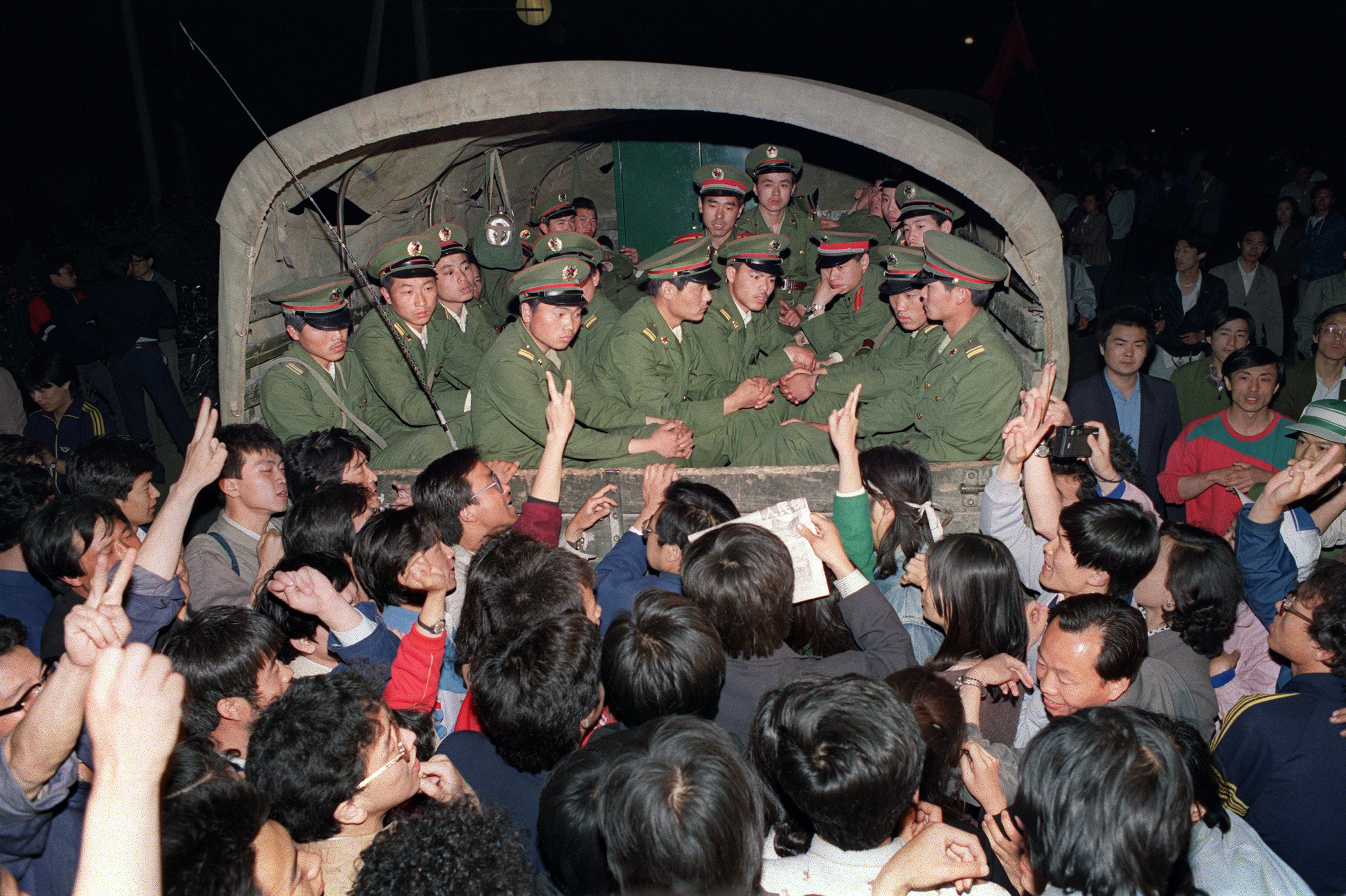 Pro-democracy demonstrators raise their fists and flash Victory signs 20 May 1989 in Beijing as they stop the military truck filled with soldiers on its way to Tiananmen Square 20 May 1989.