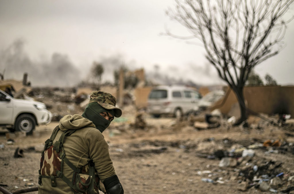 """A member of the Syrian Democratic Forces (SDF) looks on while on watch duty in the village of Baghouz in Syria's eastern Deir Ezzor province near the Iraqi border on March 24, 2019, a day after the Islamic State (IS) group's """"caliphate"""" was declared defeated by the US-backed Kurdish-led SDF."""