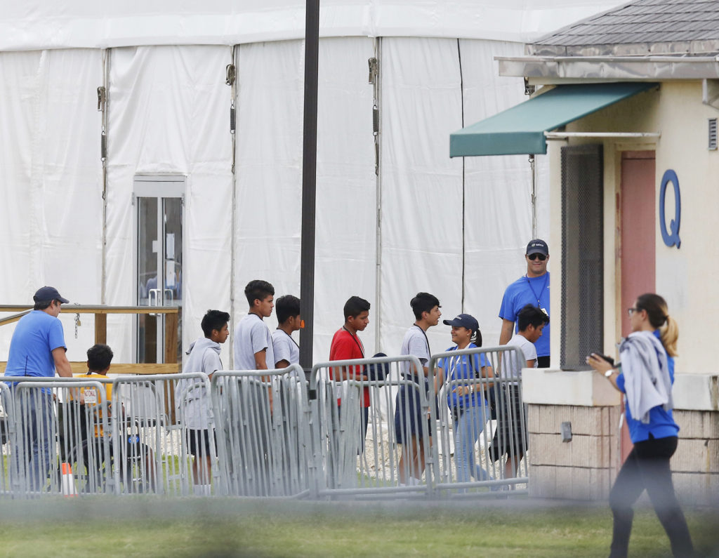 """Immigrant children walk in a line outside the Homestead Temporary Shelter for Unaccompanied Children a former Job Corps site that now houses them, on Wednesday, June 20, 2018, in Homestead, Fla. U.S. Rep. Carlos Curbelo said he found it """"troubling"""" to see two of his Democratic colleagues turned away from the Miami-area detention center for migrant children."""