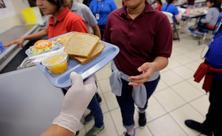 A teen reaches out to take a tray of cafeteria food.
