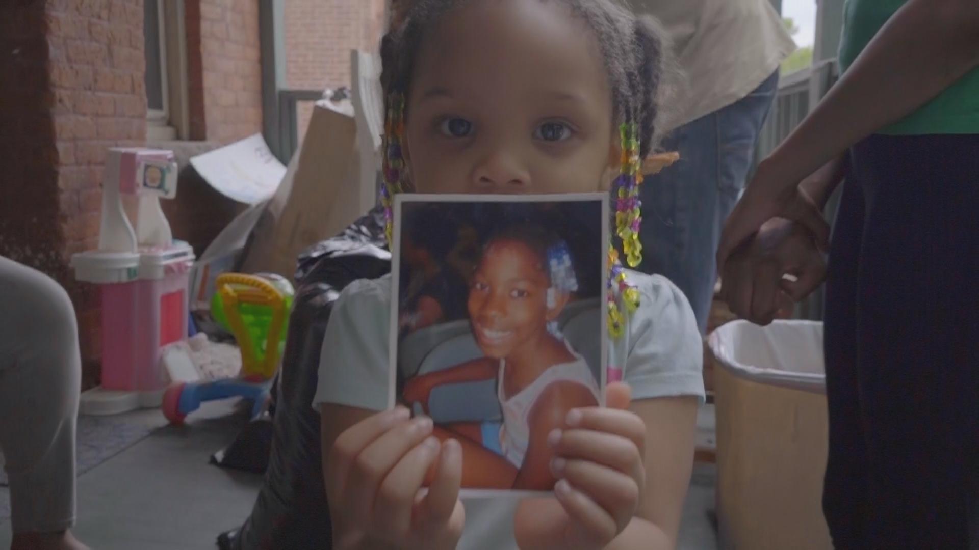 Tearah's little sister holding a photo of Tearah.