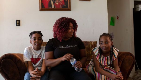 Tenise Houston, 44, with her daughter Destiny Hence, 9, and her son Darwin Hence Jr., 10, inside their home on the north side of  Flint, Mich.   in August 2020.