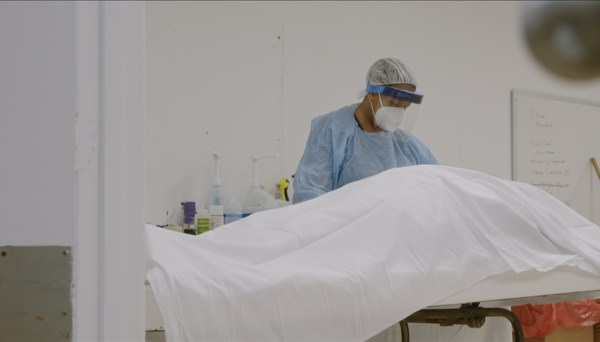 "In a still from the March 2020 documentary ""Death Is Our Business,"" an embalmer prepares a body in a New Orleans funeral home. Industry professionals say cremation is on the rise among Black and Latino families during COVID-19."