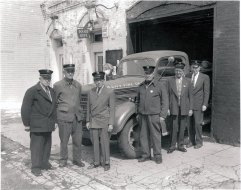 """ca.1958, Two groups of 3 firemen stand facing camera in front of fire truck parked halfway out of City Hall (painted white). Sign on truck reads """"Park City Fire Dept."""", sign on bldg. """"Police Dept."""" These men had served 50 years w/ Utah State Fireman's Association. Truck is a 1945 Mack army surplus painted olive drab; truck new to Park City in 1948"""