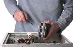 Technician Holding a Screwdriver Fixing a Computer