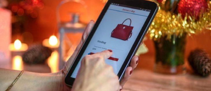 Mano di donna che tiene un tablet per fare shopping online