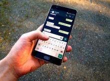 Mano che tiene uno smartphone aperto su una chat WhatsApp