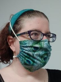 woman wearing glasses and a peacock pattern mask