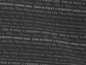 fabric with feminist-themed text in white on a black background