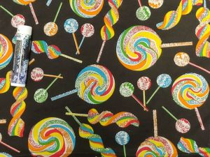 rainbow swirly candy with glitter on a black background