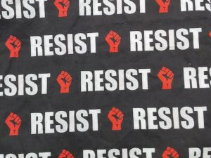 """""""Resist"""" text in a white blocky font, and a raised, clenched fist in red on a black background"""