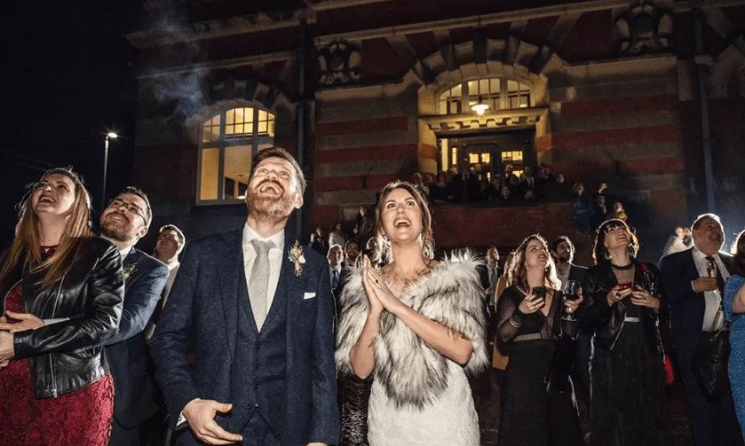 Bride, Groom and guests look up at the sky during a fireworks display for a wedding