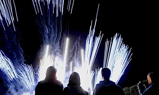 Fireworks crew silhouetted against the explosions and sparks at a training event