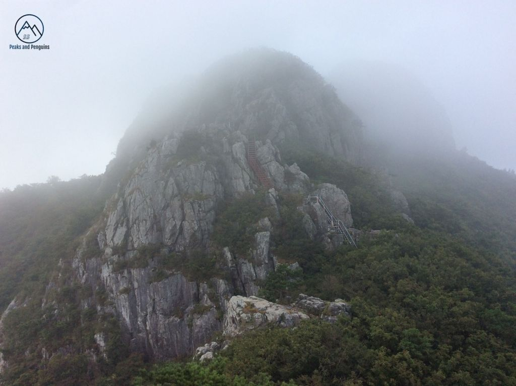 An image of the second peak of Paryeongsan. It's summit is lost in an ethereal, silvery mist. Grey rocks rise up sharply from the emerald forest. You can just make out a grey staircase and brown ladder affixed to the vertical rock surface.